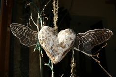 Plaster & wax over wire armature. Wings are rusty wire mesh with glitter glue.
