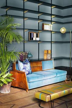 Dimore Studio living room with robin's egg blue velvet sofa and open bookcase.