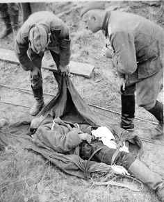 Two Germans examine Soviet POW who has died because of shock after losing his left leg.