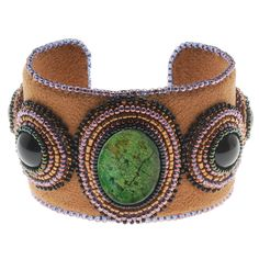 Make a bold statement by wearing this impressive bead embroidered cuff bracelet. The green magnesite gemstone cabochon contrasts beautifully against the rich brown ultra suede and accent beads. Truly stunning!