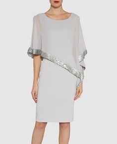 Vestido corto, en color gris plata. Con cuerpo tipo capa con ribete de lentejuelas a tono y escote redondo. Falda de tipo recto.