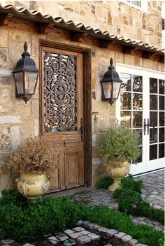 Beautiful iron work on the door, love those big old lantern lights on the sides!