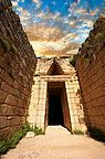 "Entrance to the Treasury of Atreus is an impressive ""tholos"" beehive shaped tomb on the Panagitsa Hill at Mycenae. The entrance has the typical square 2 upright jams covered with a lintel that weigts around 100 tons. Above the door is a trangular ""False"" or corbel arch.  Mycenae UNESCO World Heritage  Archaeological Site, Peloponnese, Greece"