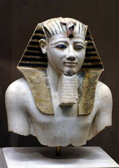Painted limestone statue of Tuthmosis III (Men-Kheper-Ra, ruled c.1479 - 1425 BC, 18th Dynasty) from the temple of Mentuhotep II at Deir el Bahri excavated by the Edouard Naville of the Egypt Exploration Fund. The face was removed in antiquity but was recovered and is now in the Egyptian Museum, Cairo. Metropolitan NY