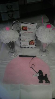 A poodle skirt place mat made out of craft felt and milkshake centerpieces made with tulle and tissue paper ;)