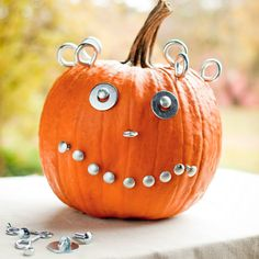 Want a pumpkin that will make everyone smile? Add goofy eyes with bolts and washers. Finish off the face with decorative upholstery nails for the smile and eye screws for hair.