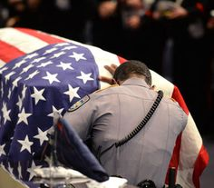 A member of Baton Rouge police Cpl. Montrell Jackson's unit kneels and touches his casket during his funeral service at the Living Faith…