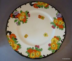 Doulton deco: unnamed plate by Robert Allen, H3501, RA255a, c1927 (pattern, impressed 2-10-27). Flowers and foliage in vibrant reds and oranges with black highlights and trim. Same floral pattern as Flamingos design.