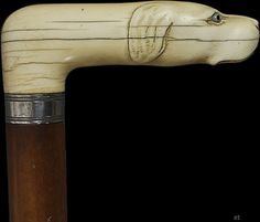 Cane with carved ivory handle done in the form of a dog's head. The ivory is realistically carved and set with two little glass eyes. The handle is mounted on a handsome wooden shaft with a band of sterling silver where the ivory attaches. The cane was made in the late 1800s, almost certainly in the United States.