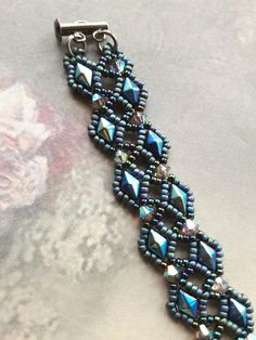 Dunkel blau metallischen Glanz Diamant Perlen Spitzen Gitter Kristall Geschenk Armreif mit Swarovski-Kristall-Elemente. Echte Swarovski Aurora Borealis beschichtet satin Farbe Kristalle umgeben eine handgenähte Netz metallischen Glanz Mitternacht Nebel und Matt blau/grau Rocailles