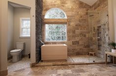 Japanese Hinoki Ofuro Tub in wet area combined with shower, hidden shower drain with pebble shower floor, travertine tile with brushed nickel fixtures.