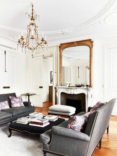 French living room with crystal chandelier, fireplace, and charcoal couches.