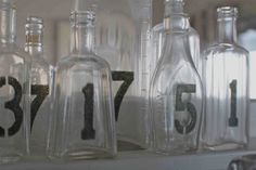 Vintage Bottles + Stenciled Numbers = I like!  These would look great with one flower stem in each one...
