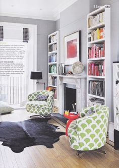 Study living room with bookshelves and KorlaHome Tub chairs in Green Kyoto Koi. Westelm persimmon side tables. Vaughan lights