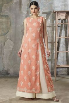Wear a tasteful appeal dressed in this ecstatic peach designer suit featuring side-front seam enriched with contrasting ivory fabric buttons followed by a slit while the entire kurta shines in ivory thread embroidered motifs in a gorgeous look! This suit is accompanied by contrasting ivory shimmer cotton palazzo pants & dupatta.