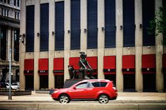 Red SUV passing the 'North Watch' at Portage and Main (Winnipeg, MB) by AJ Batac, via Flickr