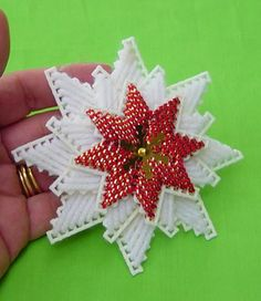 This is a vintage snowflake needlepoint plastic canvas Christmas ornament. It has red & gold metallic yarn in the middle. It has a gold col...