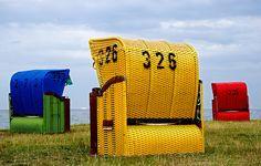 Rode, blauwe en gele strandstoelen op de Duitse Wadden van Alice Berkien-van Mil