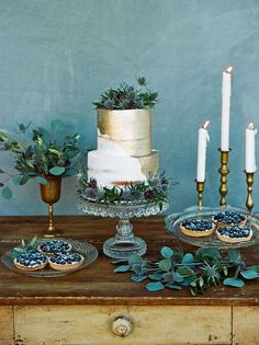 Eucalyptus greenery + brass candle stick holders and glass cake stands on the cake table, with a gorgeous tiered gilded cake and rustic individual blueberry tarts.