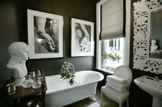 This treatment would make a small bathroom feel significant. Dark walls, crisp white contrasts - formal. Luxury in upholstered seat, clawfoot tub, ornate mirror frame, bust.