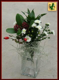 Klein tafel boeketje met Pequeña, rozenbottel uit de bloementuin, Skimmia, Aster en Tillandsia.