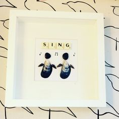 Sing!  This framed picture makes an ideal gift for the home. This piece features two people singing and original Scrabble letters stating SING!