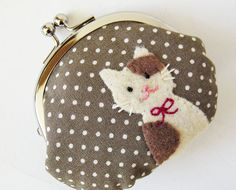 This handmade coin purse has a cream cat with brown spots appliqued on one side of the pouch. The base fabric is grayish brown with white pin dots.  It can be used not only as a coin purse but also as a jewelry case.    Dimensions:  Approximately 4 wide x 3.5 high (10cm x 9cm) at the widest/tallest part when flattened. Credit cards do NOT fit into the pouch.  The metal frame is 3.25 wide x 2 tall (8cm x 5cm)    Materials:  Outer material: 85% cotton, 15% linen  Lining: 100% cotton  Felt:...