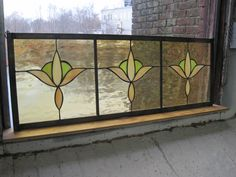 This is a cute, simple cottagey transom type of panel. It would be nice hanging in the upper part of a window or over a doorway.    It has a pale amber background with beige and light green stylized tulips.    It was done in copper foil, edged in zinc and ready to hang with hooks and chain attached.