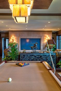 HGTV likes this game room and media room combo with large, rectangular, modern chandelier; ornate black cabinet and tan-felt-topped pool table. Large Tv, Billiard Room, Black Cabinets, Tropical Style, Mountain Resort, Pool Table, Modern Chandelier, Game Room, Living Spaces