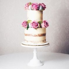 Here's a pretty semi-naked cake we created for our stand at the @risehall wedding show! Two tiers skimmed with Madagascan vanilla buttercream then adorned with large pink roses, curled parsley sprigs, grey macarons, pink macarons and white Belgian chocolate jewels splattered with gold.