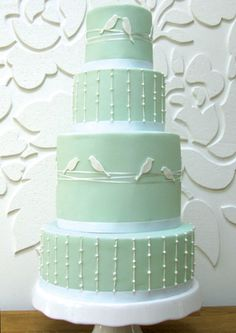Ivory birds perch along delicate ribbons with ivory piping on mint green icing, on this contemporary cake. Sweet lovebirds!