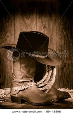 American West rodeo cowboy black felt hat atop worn western boots and spurs with old ranching rope in an antique wood barn in nostalgic vintage sepia