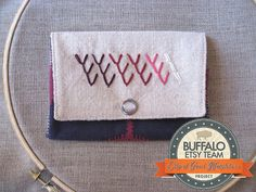 This small wallet was made by me using a combination of hand and machine sewing. It is hand embroidered with cotton embroidery floss in shades of purple