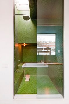 This bathroom in Berlin was designed with classic Japanese bath elements, like a small chair, deep tub and view to the roof garden, visible in the reflection. Photo: Andreas Meichsner for The New York Times