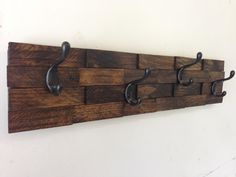 "This rustic coat rack has a lot of interesting details since it is made from so many individual pieces of wood. This unique rack is completely handmade. The rack is stained in a beautiful dark walnut color and sealed to protect the wood. The coat rack has 4 heavy duty matte black coat hooks and is 25"" long. This coat rack is also available with 6 hooks (35"" long), 5 hooks (29"" long), and 3 hooks (20"" long)."