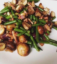 Haricots Verts met Spek en Champignons  Maak de boontjes schoon en snij ze in stukjes. Kook ze vervolgens even voor. Snijd de ui en knoflook fijn Doe de spekjes in een wok zonder boter of olie. Wok op middelhoog vuur. Na 2 minuten ook de ui en knoflook toevoegen. Als de ui glazig wordt, voeg je de boontjes en champignons toe. Laat het geheel nog 5 minuten roerbakken.