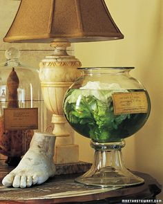 Specimen Jars  Use a side table to hold the work of a mad scientist. Fill a few glass vessels more than halfway with colored water (mix 3 drops green or 1/2 drop red food coloring in water; add a few tablespoons milk for murkiness). Peel off outer layers of a cabbage head for a brain specimen; use a fennel bulb with the fronds cut off for a heart.  With a glue stick, attach a printed or written label on the container.