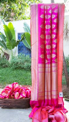 This iridescent fuchsia pink and orange Benares silk has intricately woven antique gold zari floral bhuttas all over. The fuchsia pink and gold zari with temple design border & pallu gives the ...