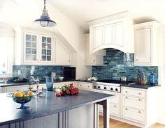Blue glass backsplash with white cabinets