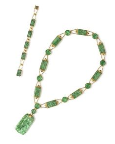 An 18 Karat Yellow Gold and Jade Demi Parure, Tiffany and Co., Circa 1925,   consisting of a necklace composed of 18 round and rectangular carved jade sections joined by intricately engraved gold terminals in a foliate motif and chain link, together with a matching bracelet composed of five carved jade plaques.