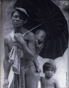 Babywearing Filipino father. From Luzon, the Philliphines. By John Everard. Identified as a headhunter, so Bontoc/Igorot tribe.