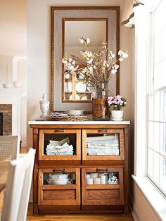 """Antique grain bin re-purposed as dining room storage that I styled with table linens & candles for Better Homes & Gardens """"100 Ideas for Flea Market Style"""" magazine."""