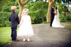 Timeless photo idea with ring-barer and flower girl in the foreground and Bride and Groom in the background.