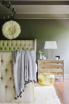 A tufted bed, golden Moroccan pouf, and chic decor make this bedroom seriously sophisticated. The addition of the olive green walls makes this master suite both soothing and serene.