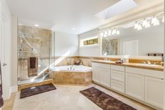 Contemporary Master Bathroom with Complex granite counters, Stone Tile, Limestone Tile, Wall sconce, High ceiling, Skylight