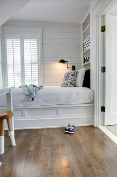 Cottage style bedroom features shiplap paneled walls framing plantation shuttered windows and built-in shelving over the built-in bed with wainscoting trim which is dressed in white bedding and a navy botanical pillow lit by an oil-rubbed bronze wall lamp across from a white desk with Serena & Lily Dip Dyed Stool tucked below.
