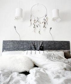 peinture murale blanche, suspensions blanches décorées de nacre, capteur de rêves et coussins blancs dans la chambre bohème