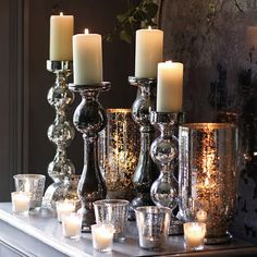 Silver candlesticks and white candles on a mantle for Christmas Pillar Candle Holders, Candle Lanterns, Pillar Candles, Candle Sticks, Candleholders, Hurricane Lamps, Glass Holders, Silver Candlesticks, Silver Christmas