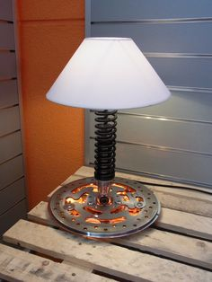 """Faak Brake"" incorporates a shock from an American motorcycle and uses a brake disk as a base. We added some LED lighting tech to turn this lamp into an exceptional design object on a table or desk in any environment. We have a wide selection of different shades available, allowing to give this lamp your personal note. See more of our designs at www.cruisindesign.com or contact us for more information. All our designs come with a lifetime warranty and we ship world wide."