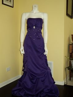 This purple, satin, strapless gown has beautiful detail on the front and pickups all around for a very elegant look!